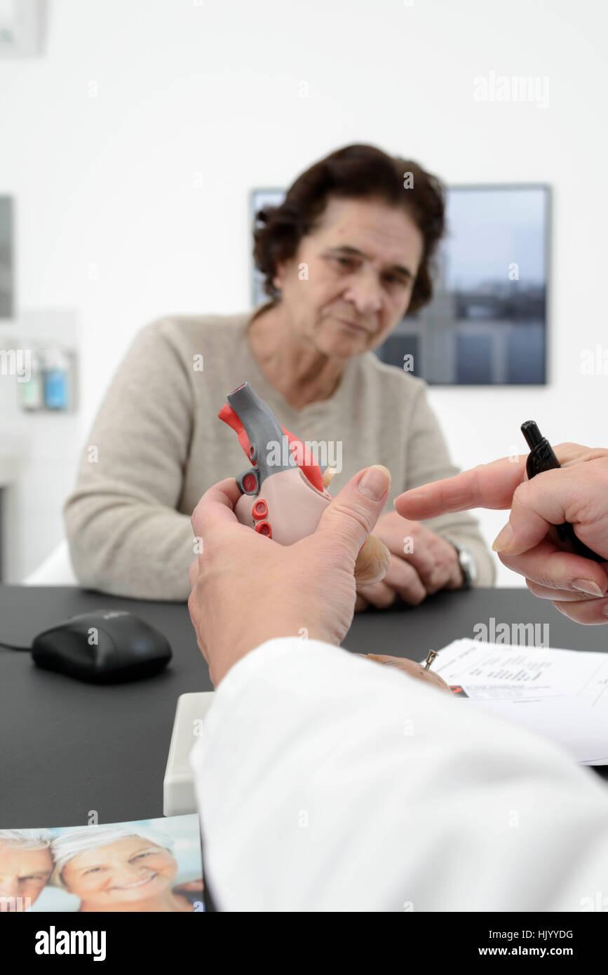 Cardiologue explique le cœur humain à un patient de sexe féminin senior Photo Stock
