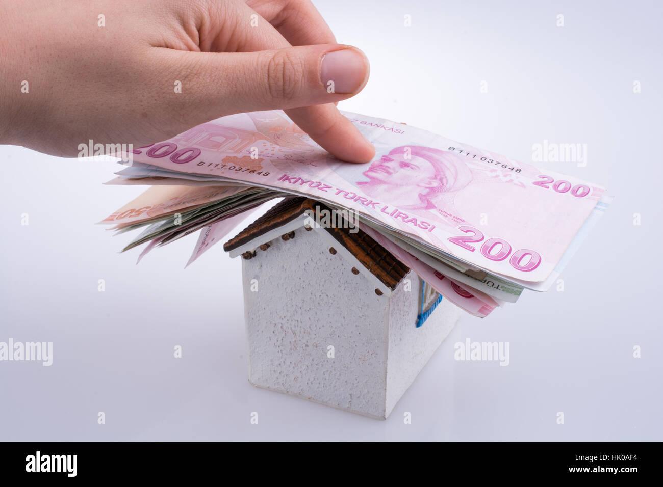 Main tenant Livre turque billets sur le toit d'une maison modèle sur fond blanc Photo Stock
