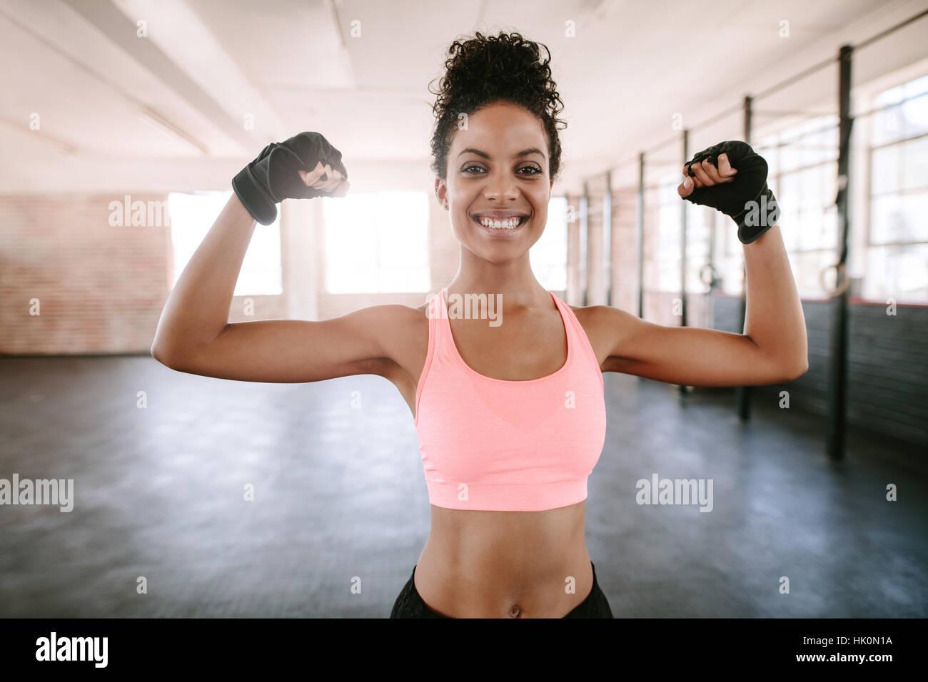 Portrait of young woman flexing muscles et remise en forme de sourire. Modèle féminin en Afrique sportswear Photo Stock
