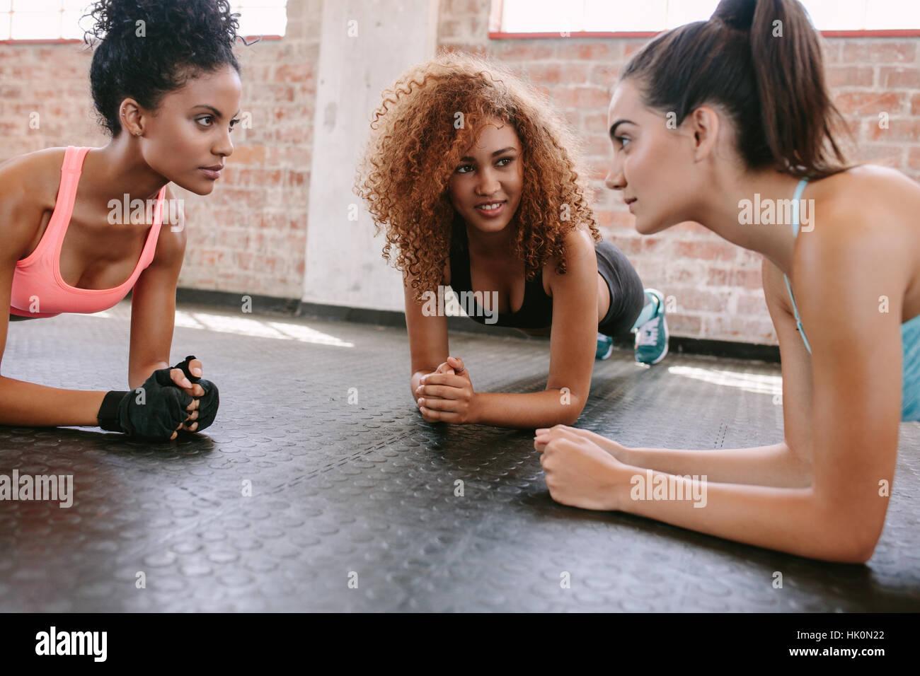 Trois jeunes femmes faisant pompes ensemble dans une salle de sport. Groupe de femmes travaillant à l'healthclub. Banque D'Images