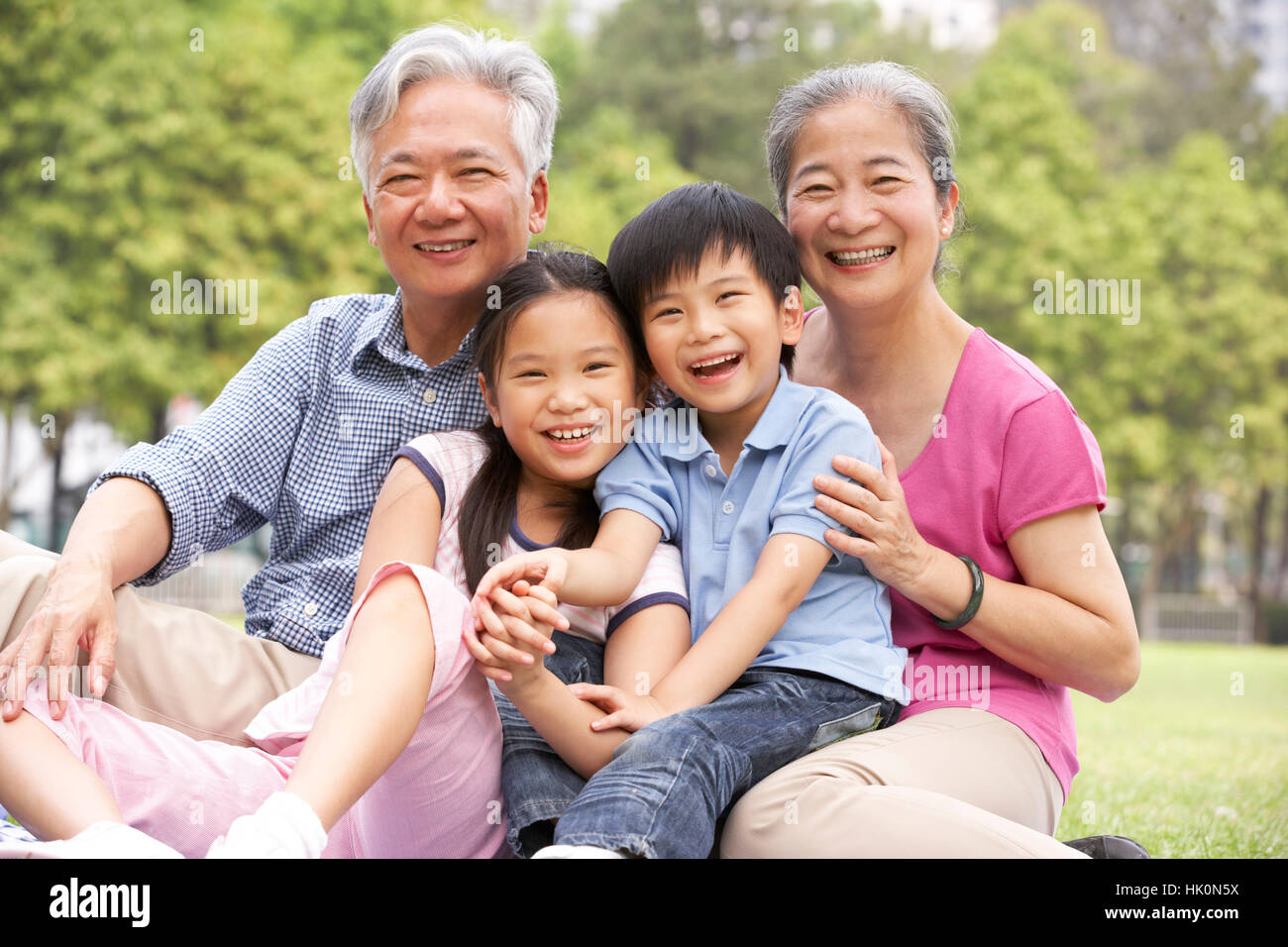 Les grands-parents chinois assis avec petits-enfants dans le parc Banque D'Images