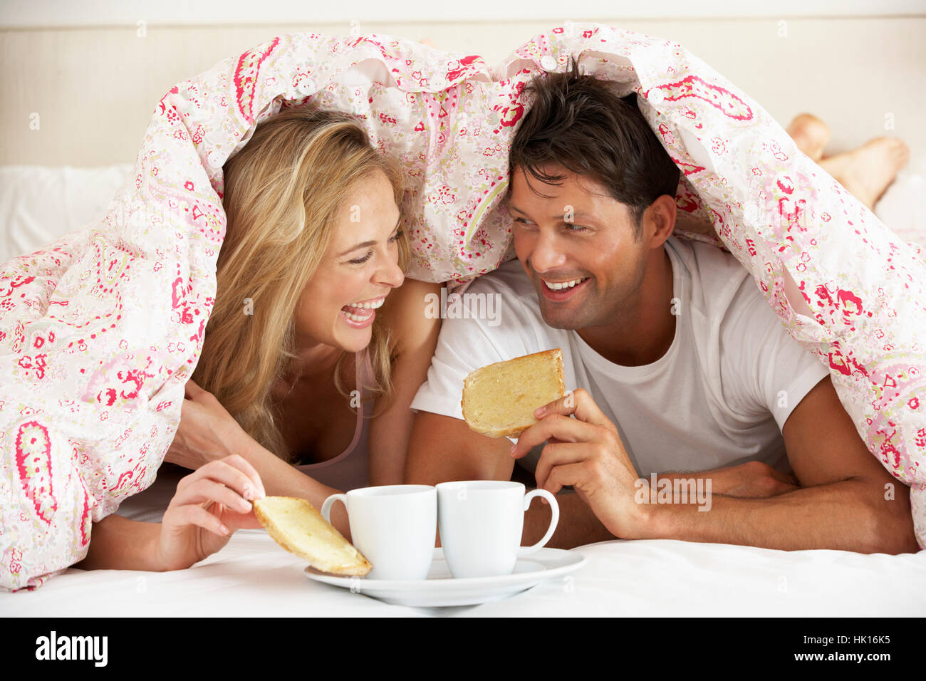 Couple se blottit sous couette Eating Breakfast Banque D'Images