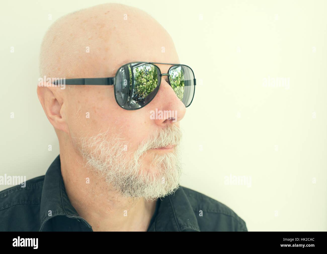 Vieil Homme à lunettes cool à la route. Jardin Vert reflète dans les lunettes. Banque D'Images
