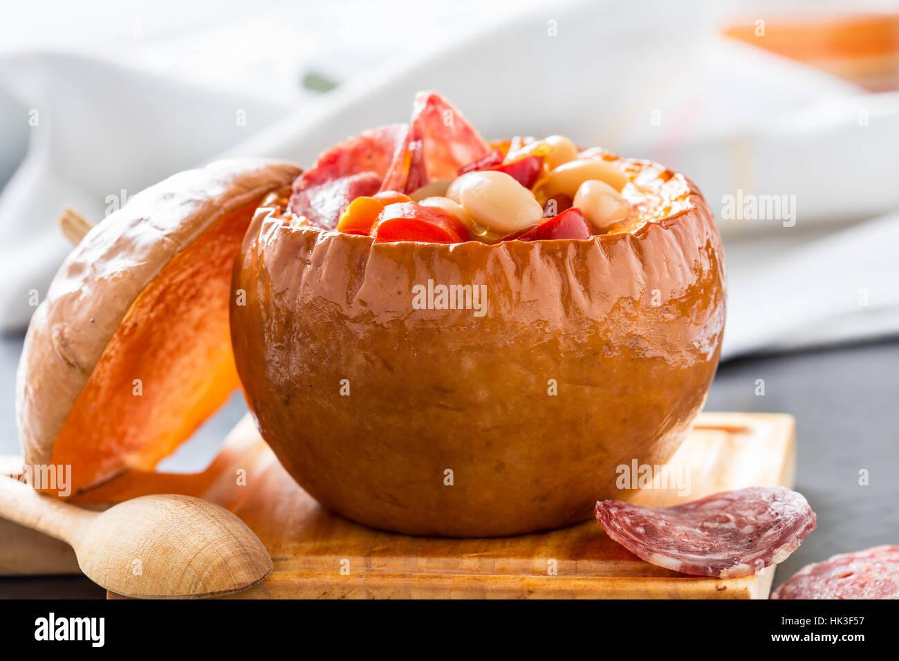 Le haricot blanc et rouge légumes ragoût dans des bols de potiron servi sur planche de bois Photo Stock