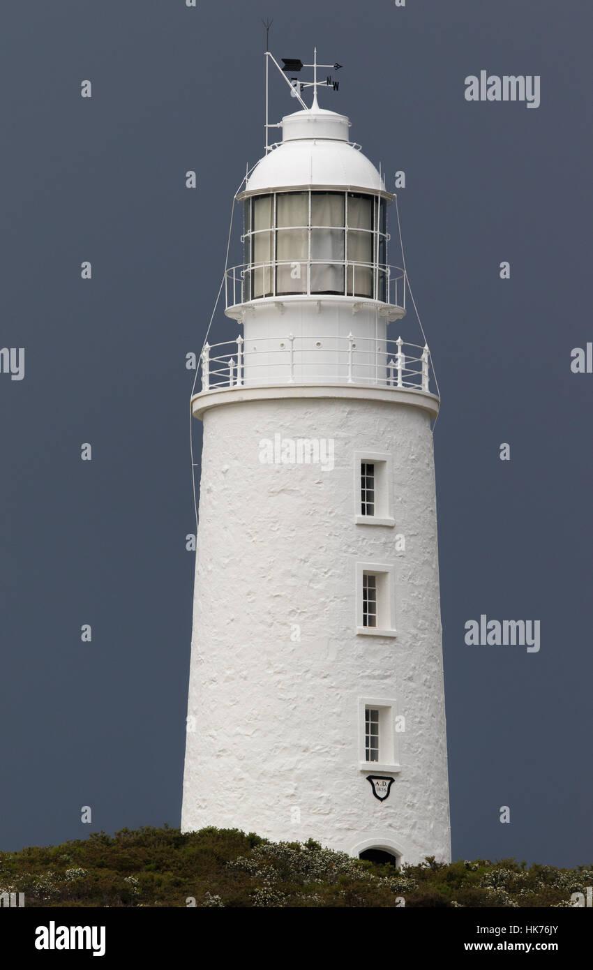 Bâtiment blanc de l'île Bruny Leuchtturm contrastant contre fond de nuages sombres Photo Stock