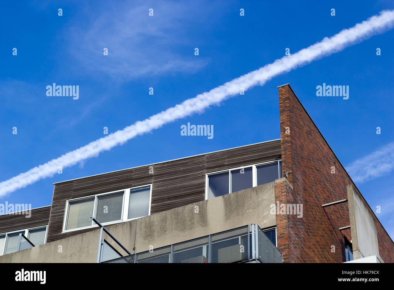 Amsterdam, Pays-Bas - le 20 janvier 2017: Avions traînée de vapeur au-dessus d'un bloc d'appartement Photo Stock