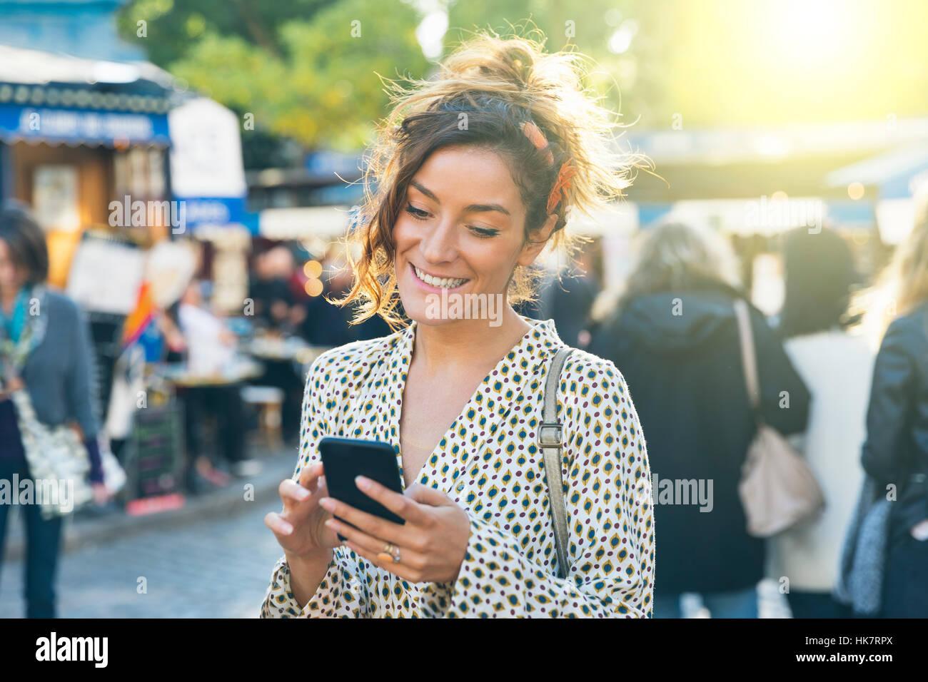 Paris, jolie femme visiter Montmartre et à l'aide d'un téléphone intelligent Banque D'Images