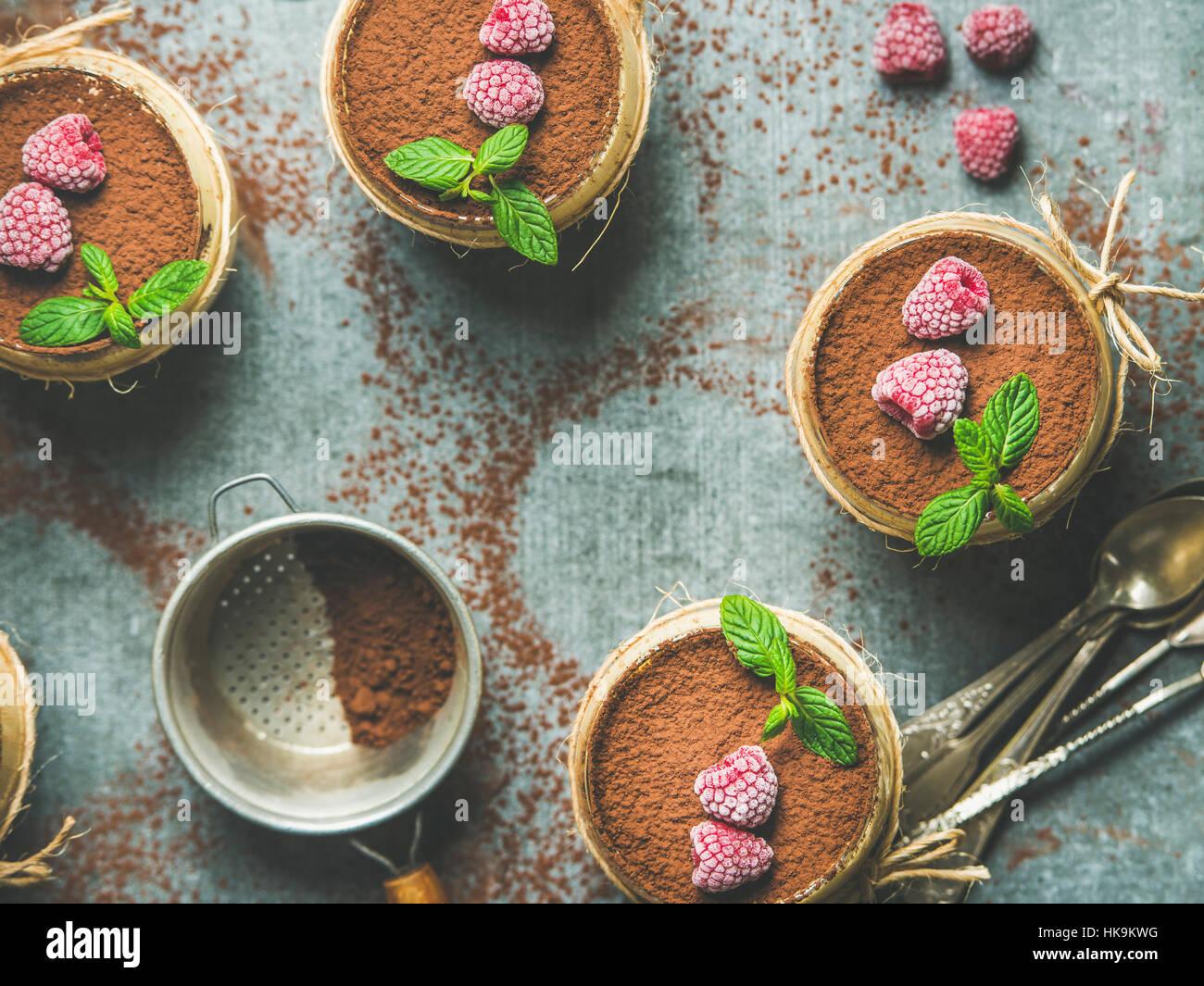 Tiramisu dessert italien fait maison servi dans des verres individuels avec les feuilles de menthe et de poudre Photo Stock