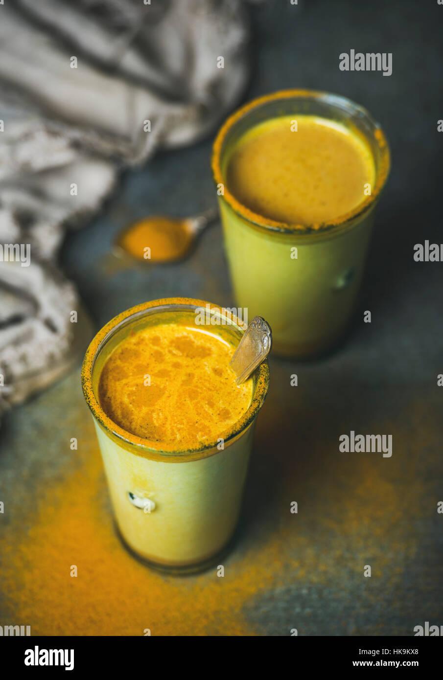 Poudre de curcuma avec du lait d'or dans les verres sur fond sombre. La santé et de l'énergie Photo Stock