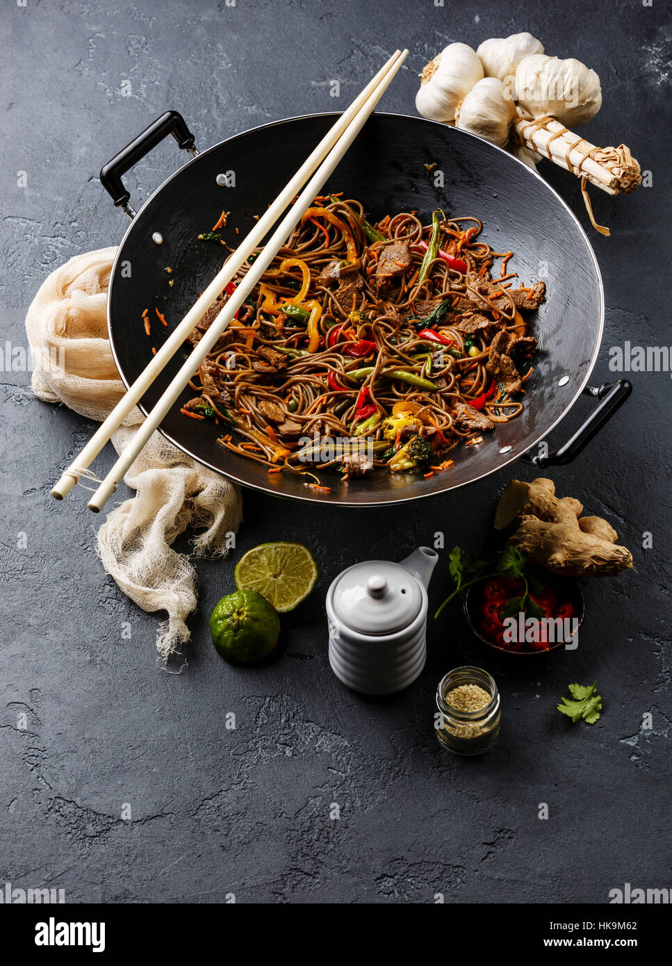 Fast food asiatique nouilles soba sautés au boeuf et légumes en wok casserole sur fond noir en sombre Photo Stock