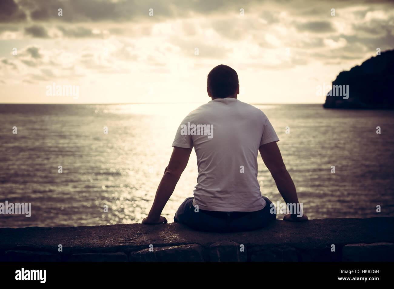 Homme seul à la recherche d'espoir à l'horizon avec la lumière du soleil pendant le coucher Photo Stock