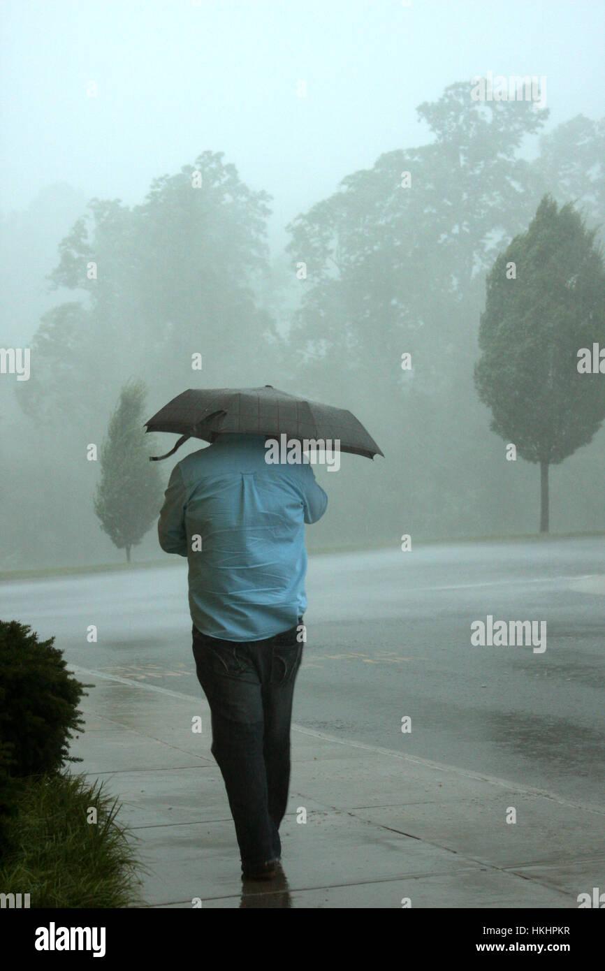 Homme avec une marche sous la pluie parapluie Photo Stock