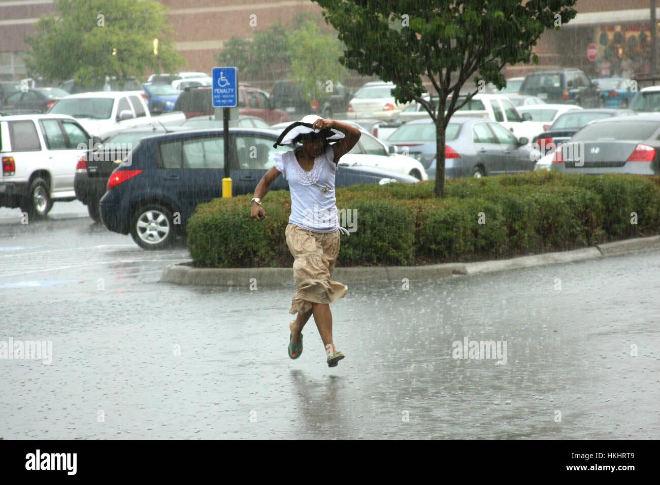 Femme en marche à l'abri de fortes pluies estivales Photo Stock