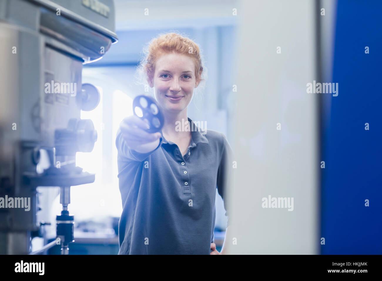 Jeune ingénieur femelle holding pignon dans une installation industrielle, Freiburg im Breisgau, Bade-Wurtemberg, Photo Stock