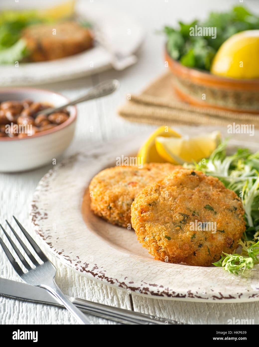 Délicieuses galettes de poisson pané avec des haricots blancs. Photo Stock