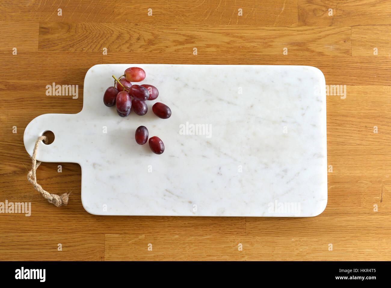 Plateau de fromage en marbre blanc dans une cuisine avec du fromage et du raisin Photo Stock