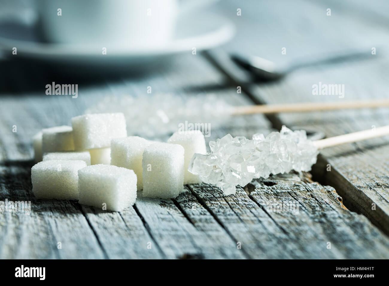 Le sucre cristallisé sur bâtonnet de bois et des morceaux de sucre sur la table en bois. Photo Stock