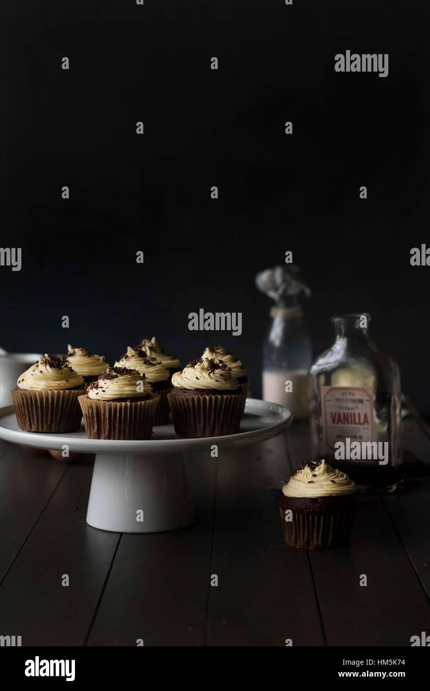 Cupcakes en cakestand avec des bouteilles sur le tableau sur fond noir Photo Stock