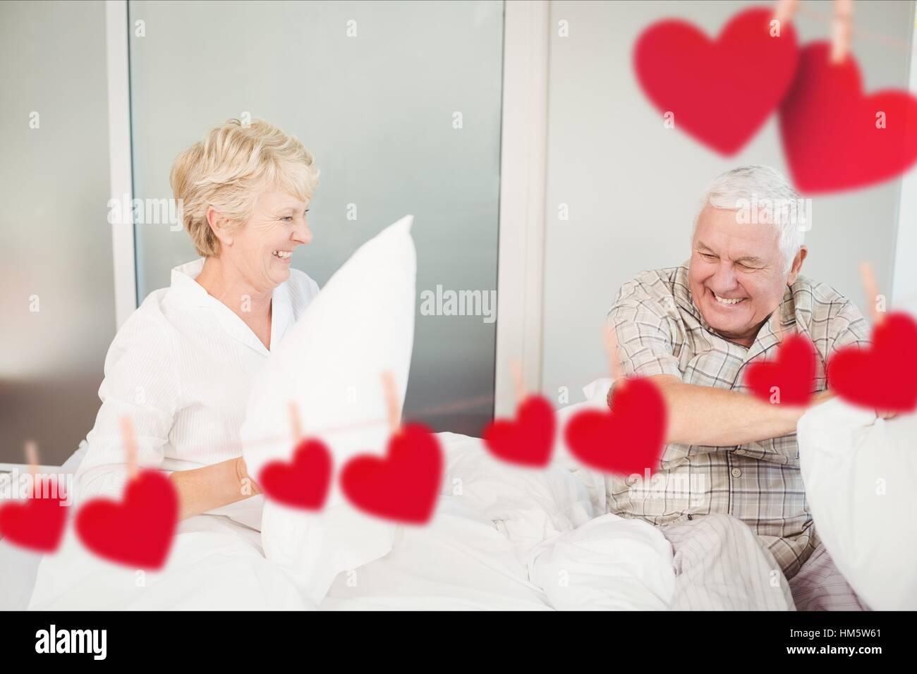 Senior couple having pillow fight dans la chambre à la maison Photo Stock