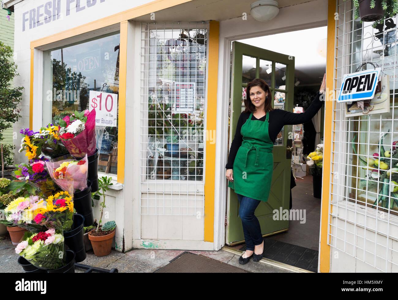 Portrait of female florist standing in doorway of flower shop Photo Stock