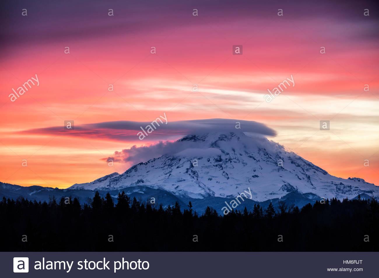 Un nuage lenticulaire caps le sommet du Mont Rainier au lever du soleil dans cette vue de Bonney Lake, Washington. Photo Stock