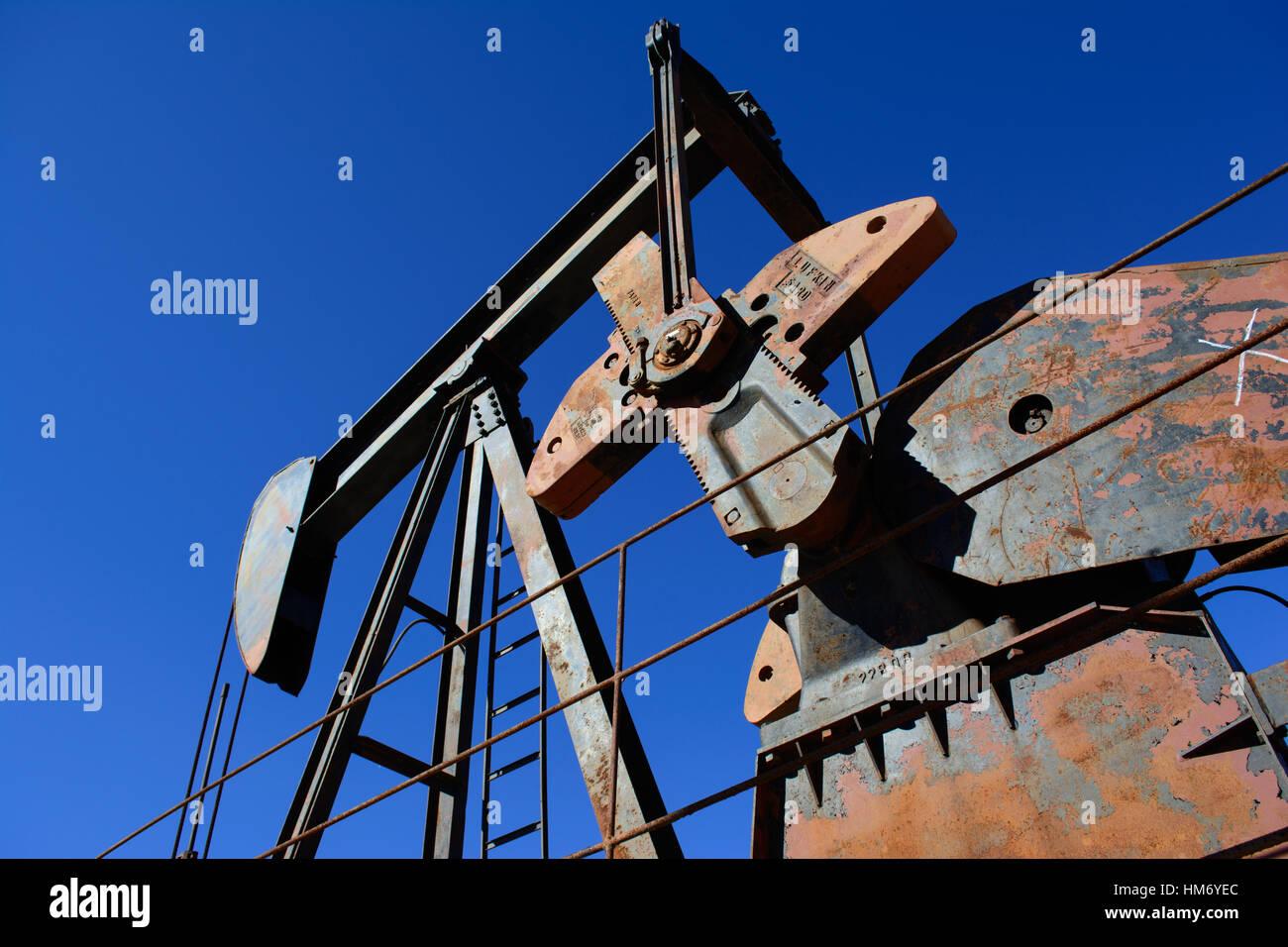 Rusty Oilfield Pumpjack (10-12) sur un puits. Fond de Ciel bleu clair. La vie illustre oilfield, secteur du pétrole Photo Stock