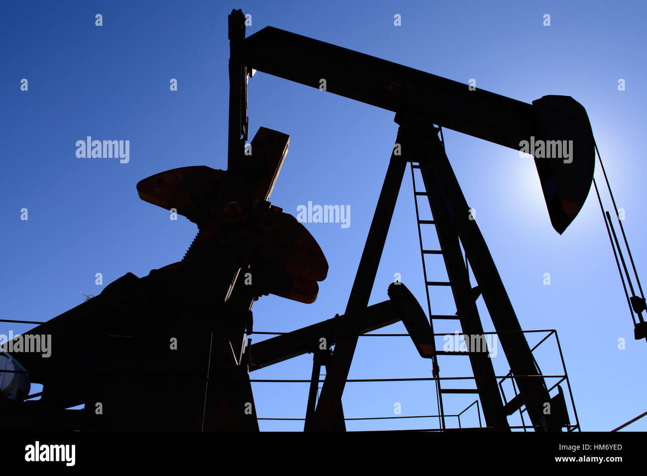 Pumpjack Oilfield, rouillé et vieux, silhouetté par le soleil. Fond de Ciel bleu clair. La vie illustre Photo Stock