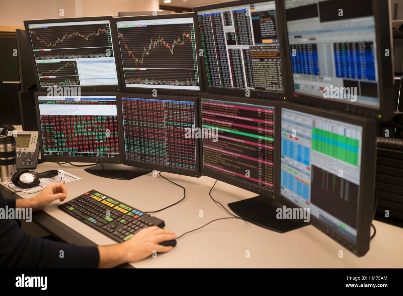 Jeune homme travaillant sur le groupe de moniteurs d'ordinateur Photo Stock