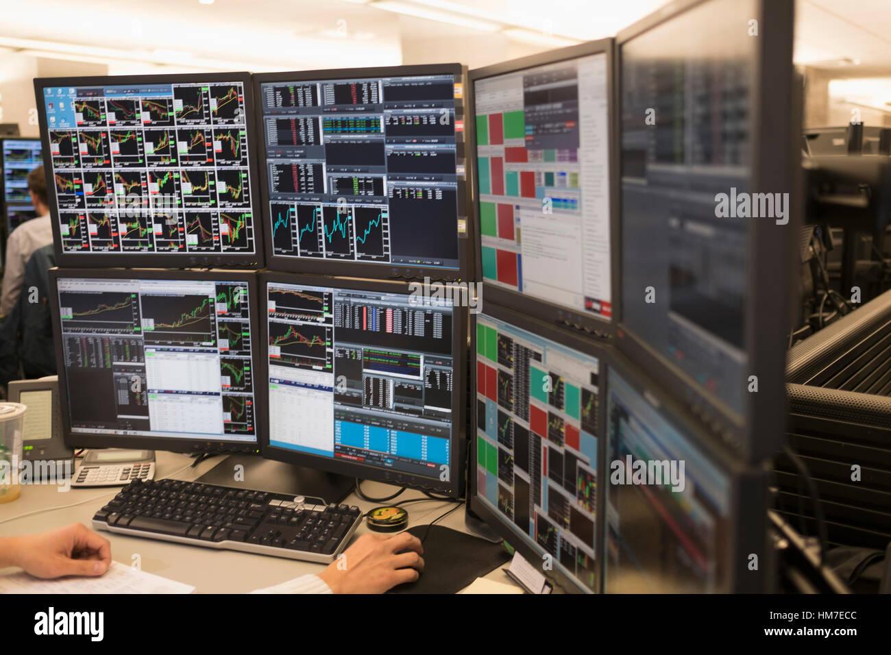 Jeune homme travaillant sur le groupe de moniteurs d'ordinateur Banque D'Images