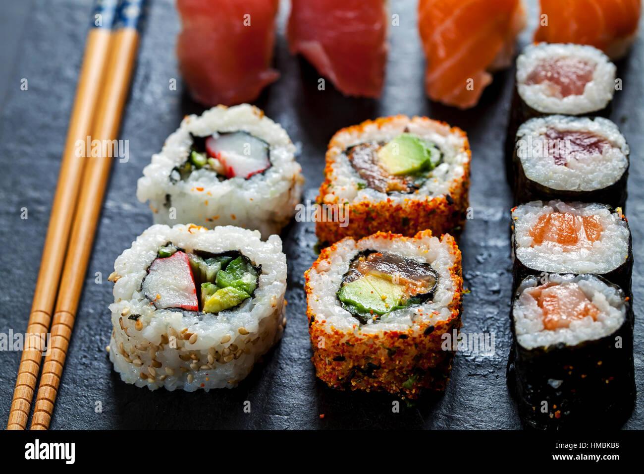 Le saumon et le thon sushi sur la plaque en ardoise noire Photo Stock