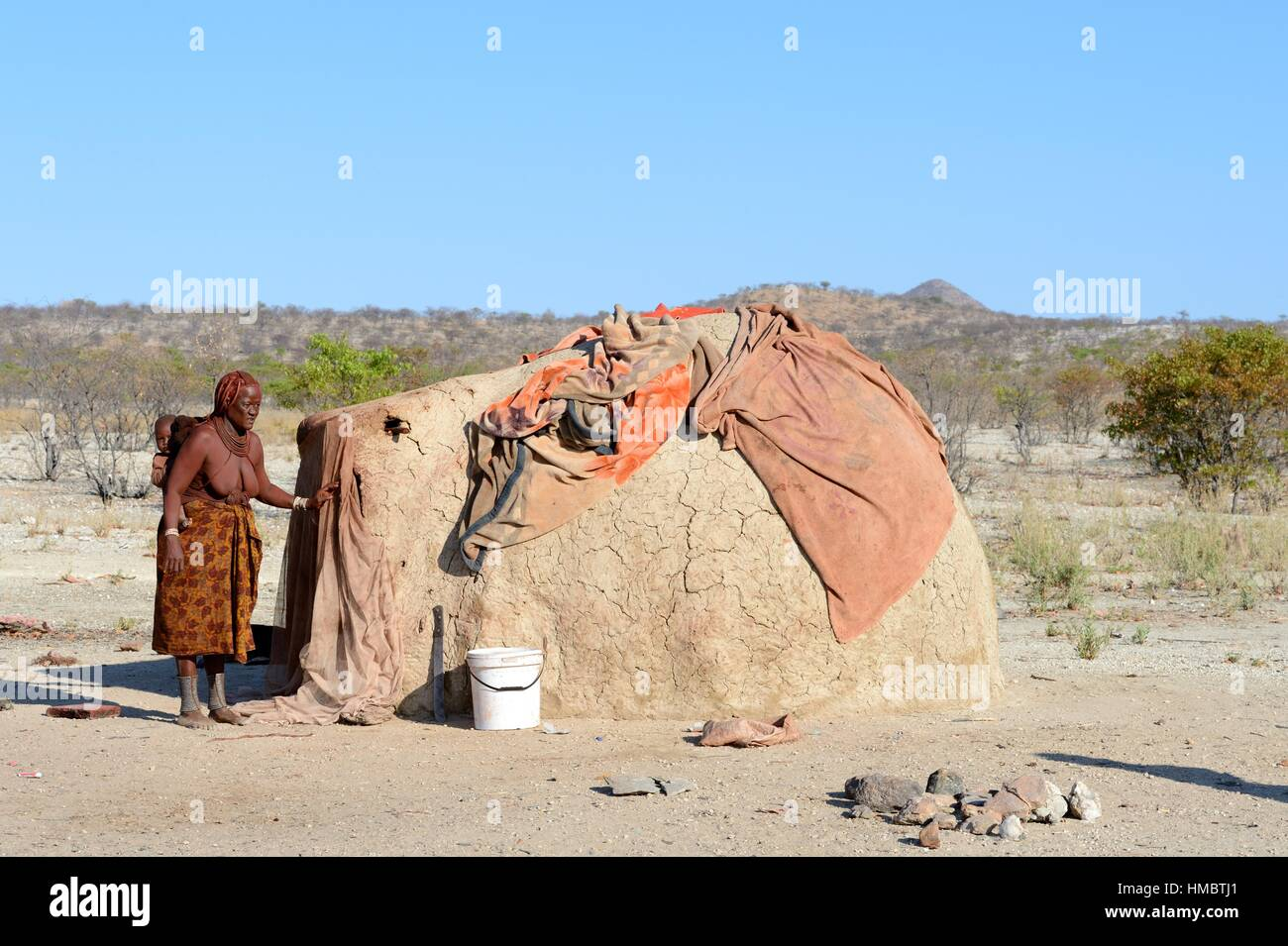 Femme Himba traditionnel à côté de cabane de torchis. Kaokoland, la Namibie. Photo Stock