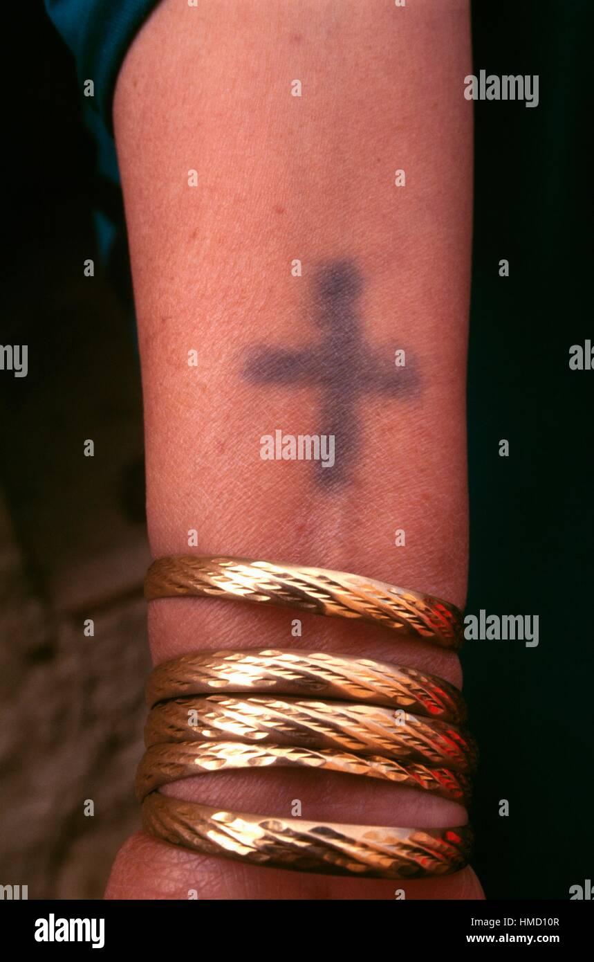 bracelets en or porté sur le bras d'une femme avec un tatouage, l