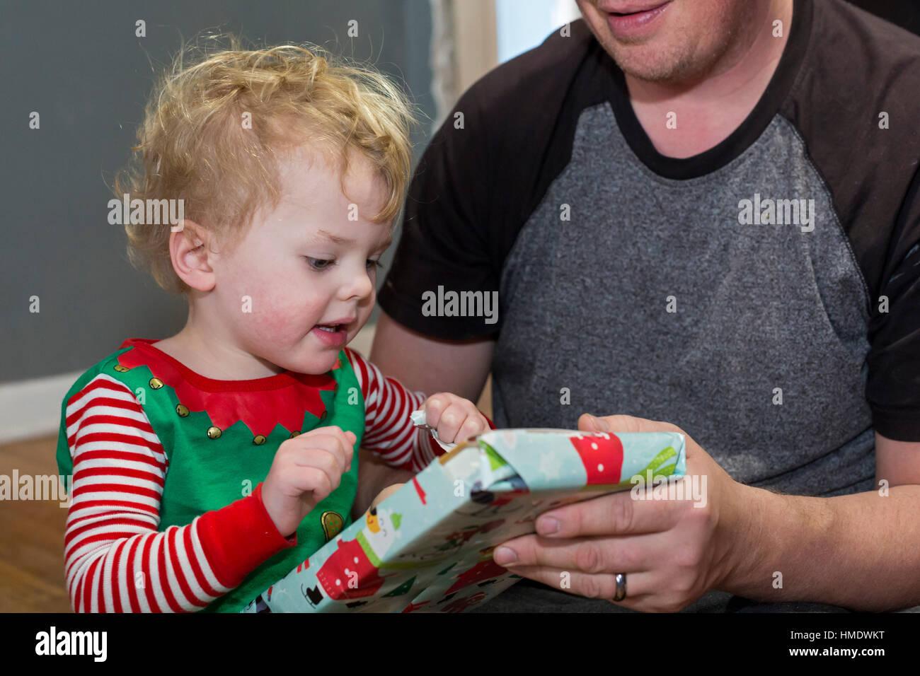 Denver, Colorado - Adam Hjermstad Jr., 2 1/2, ouvre un cadeau de Noël tenu par son père, Adam Hjermstad Photo Stock