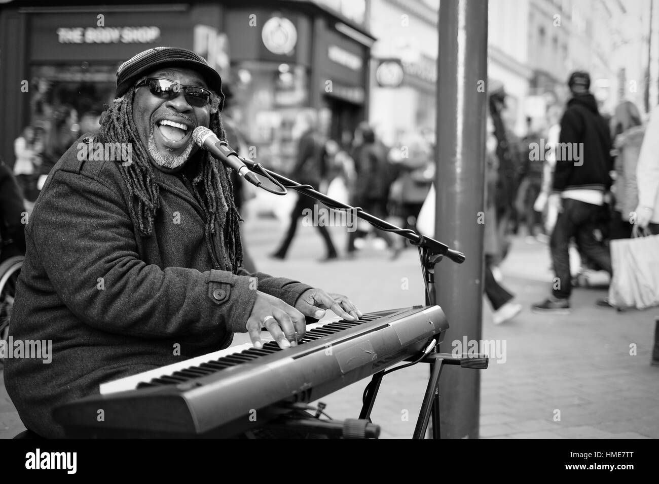 Un homme avec des dreadlocks afro et lunettes joue du clavier dans la rue d'une ville britannique. Banque D'Images