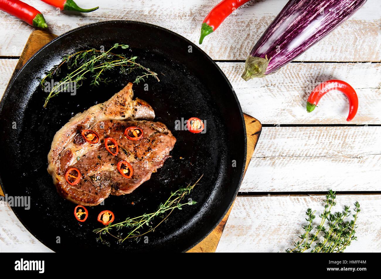 La viande avec les épices dans une casserole, romarin, et Hot Chili Peppers sur un arrière-plan de table Photo Stock