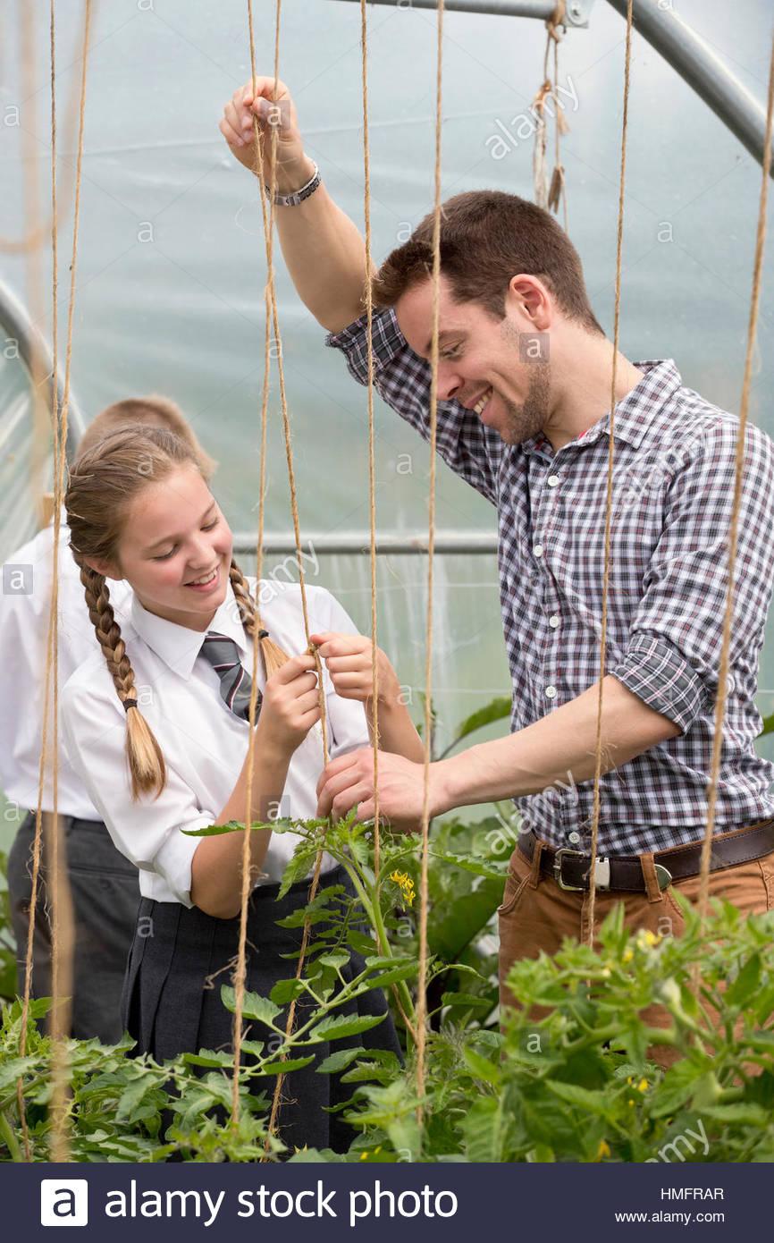 Enseignant de sexe masculin et de l'apprentissage d'écolière de filets de jardinage plants in Photo Stock