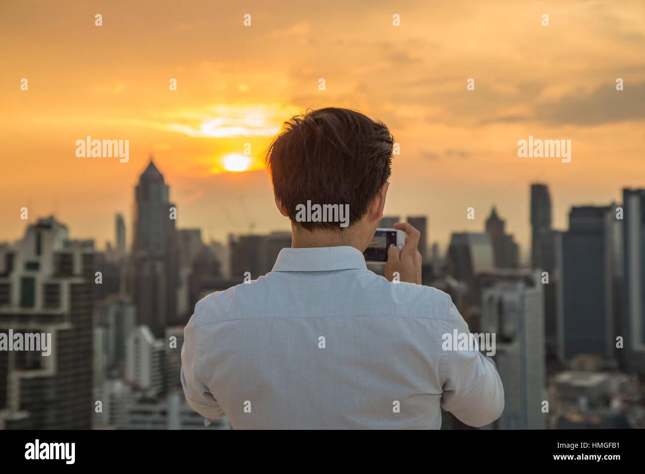 L'homme prend une photo de paysage urbain, la ville de Johannesburg et le coucher du soleil avec le smartphone. Photo Stock