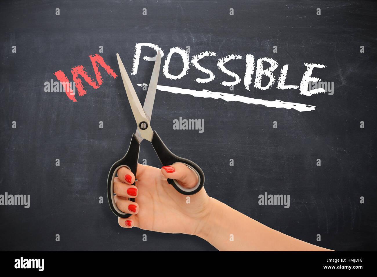 """Message de motivation sur tableau noir avec des ciseaux de coupe femme avec le mot """"impossible"""", tournant dans la mesure du possible Banque D'Images"""