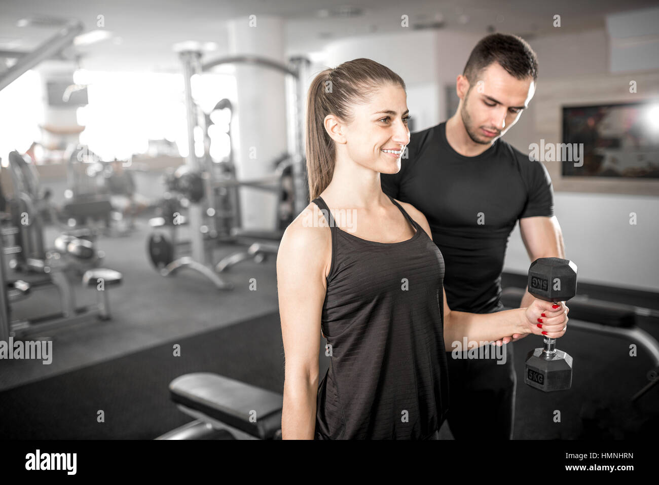 Young adult woman working out in gym, faire des biceps avec l'aide de son entraîneur personnel. Photo Stock