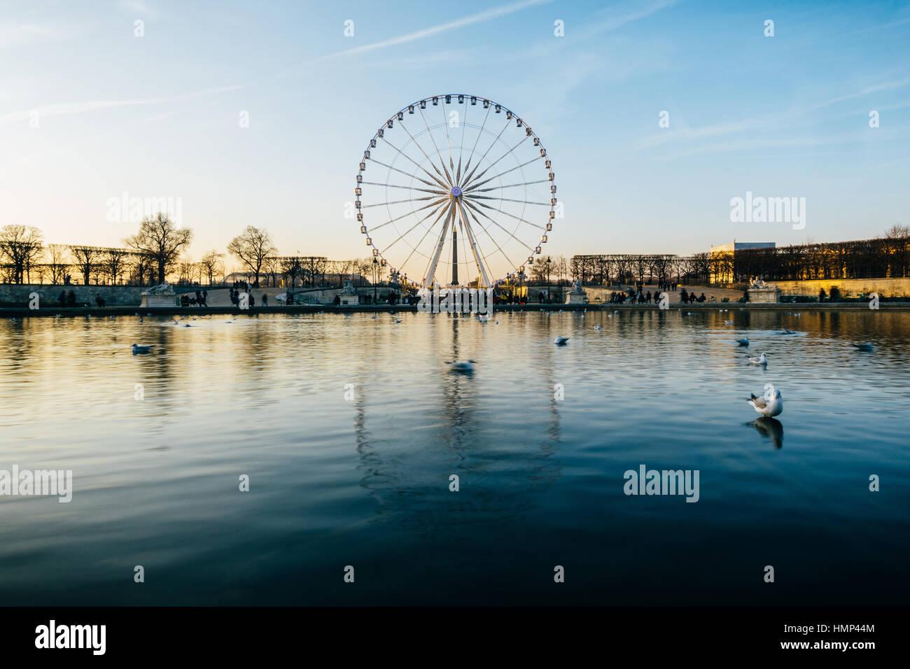 La grande roue sur la place de la Concorde se reflète sur la surface de l'eau de l'étang dans le jardin des Tuileries, Banque D'Images