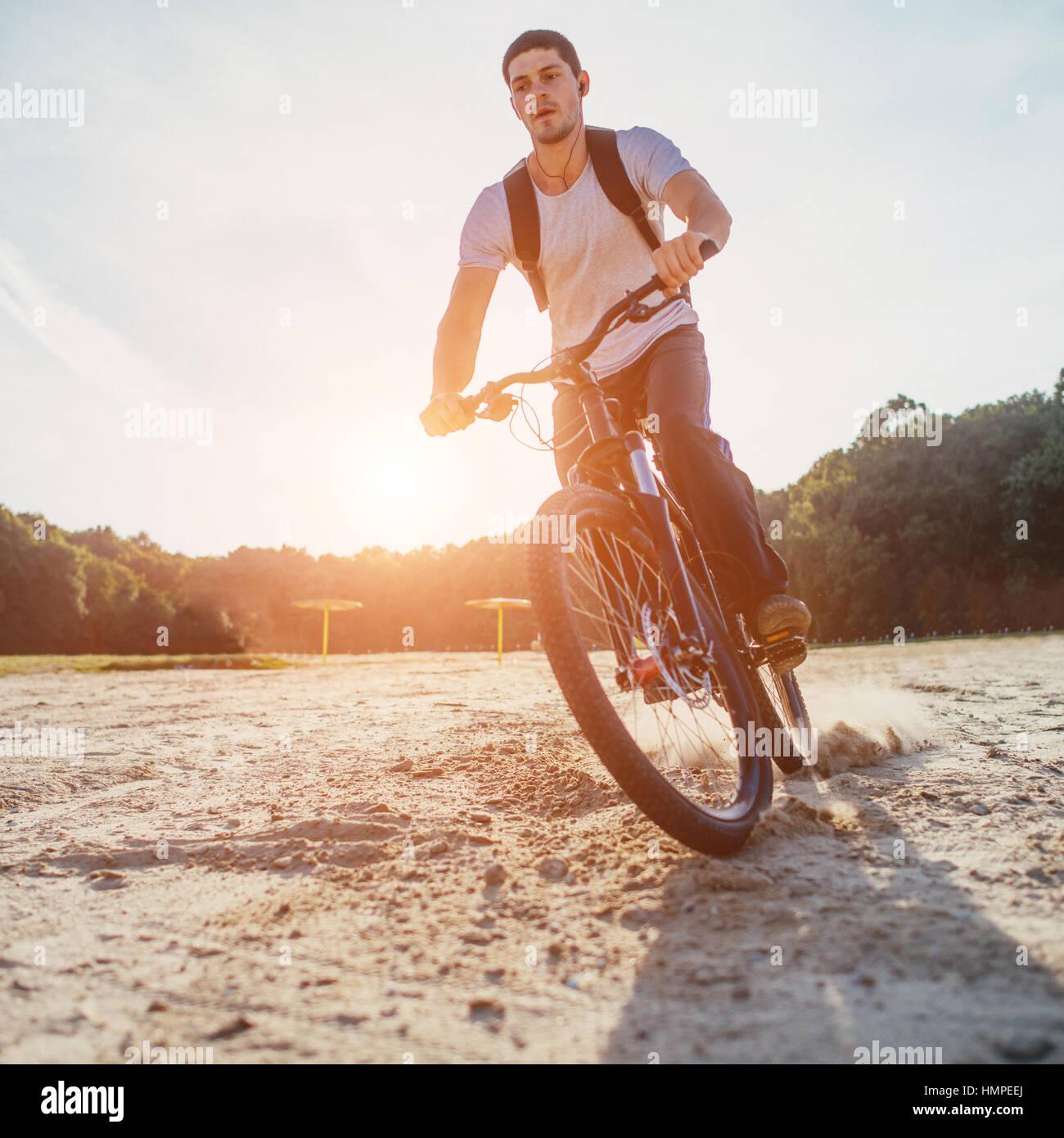 Biker à cheval le long de plage au coucher du soleil Photo Stock
