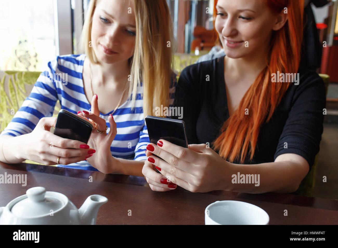 Deux femmes s'amuser au café et à la recherche de téléphone intelligent. Photo Stock
