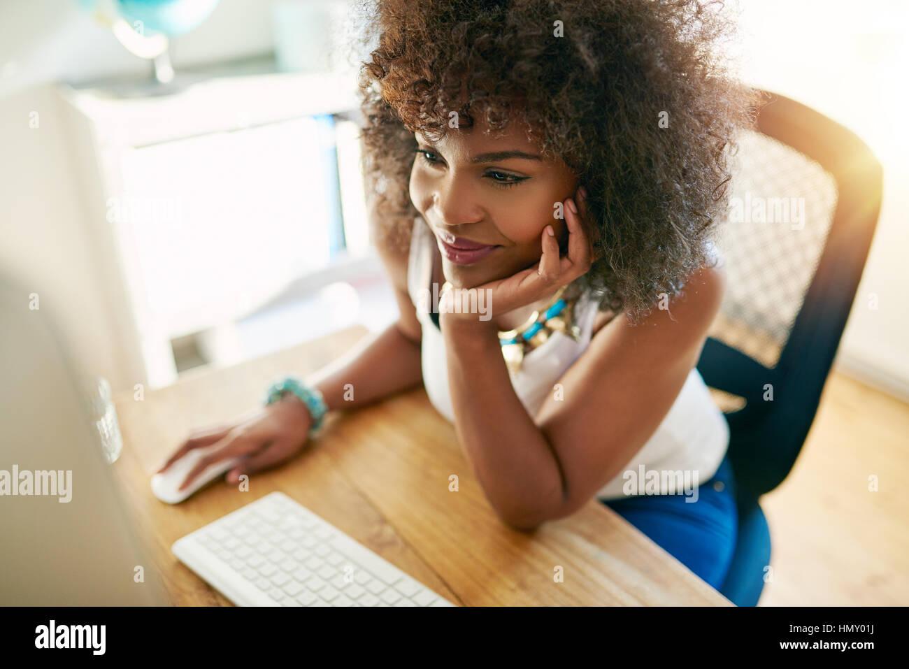 Jolie jeune fille afro-américaine travaillant sur pc et sourit à l'arrière-plan flou à l'intérieur. Photo Stock