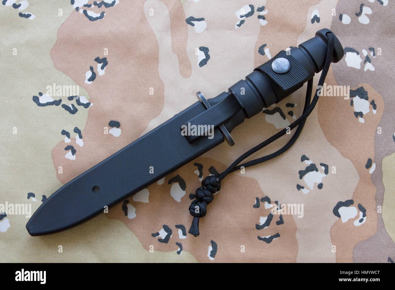 Couteau tactique dans un cas sur le sable camouflage. Le couteau pour l'armée. Photo Stock