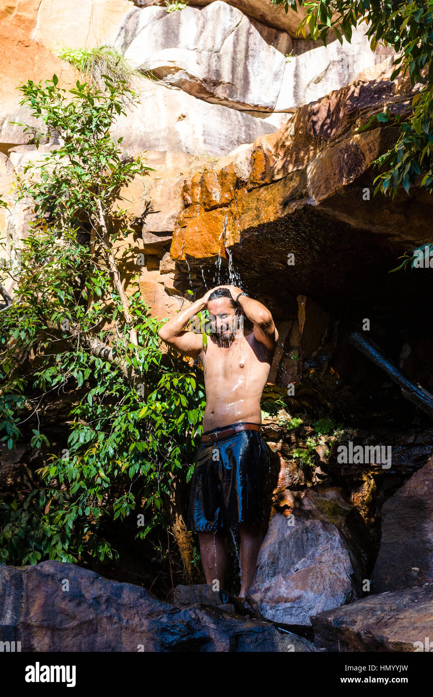 Un homme prend une douche fraîche sous une petite chute d'eau douce dans un désert gorge. Photo Stock