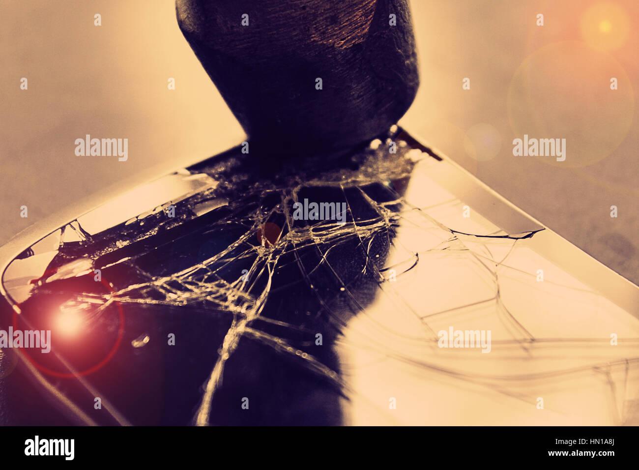 L'écran du téléphone cassé et un marteau sur background,un coup de marteau sur le téléphone Photo Stock