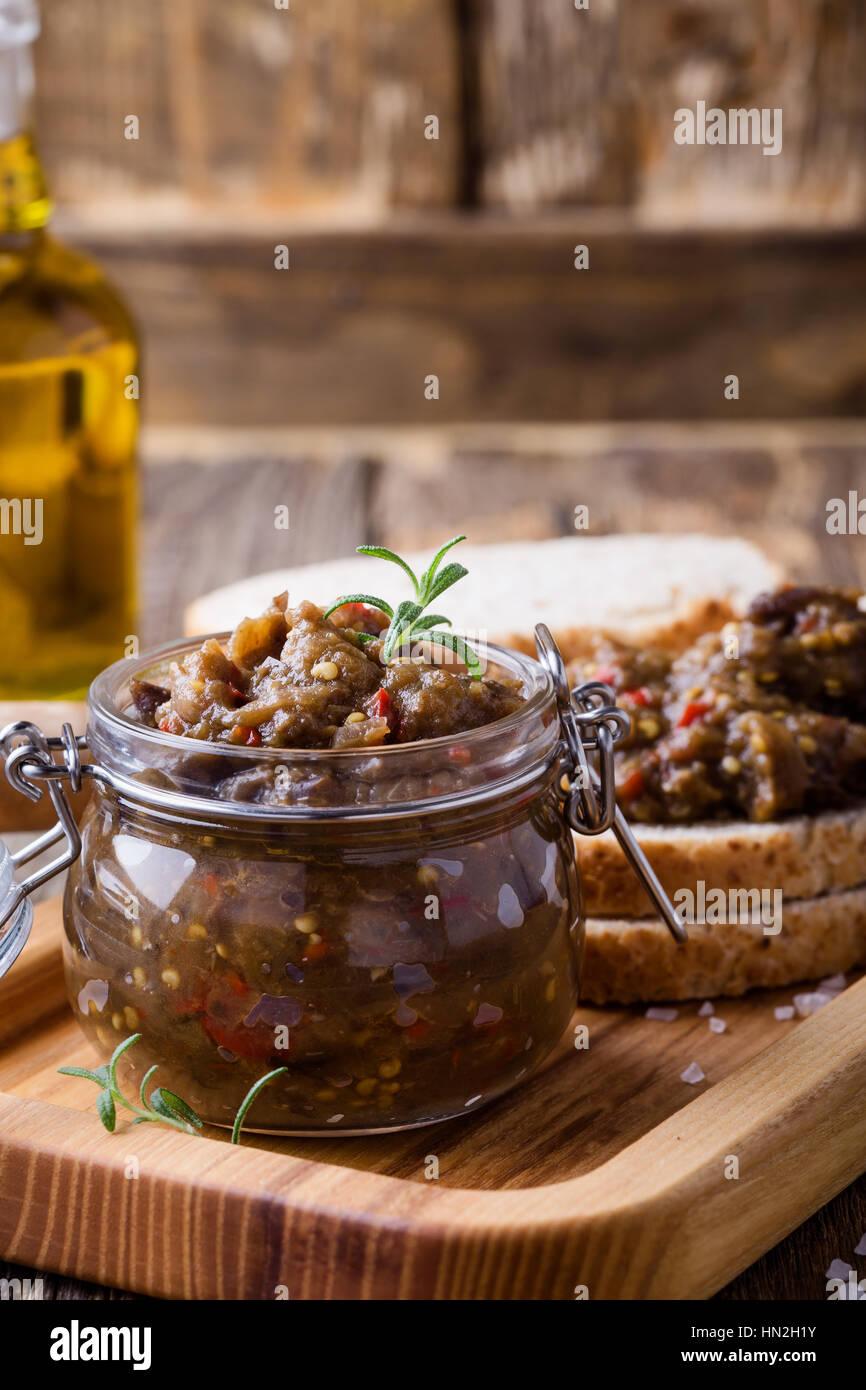 Des pate de l'aubergine. Coller dans un bocal en verre sur la table en bois rustique. La nourriture végétarienne Banque D'Images