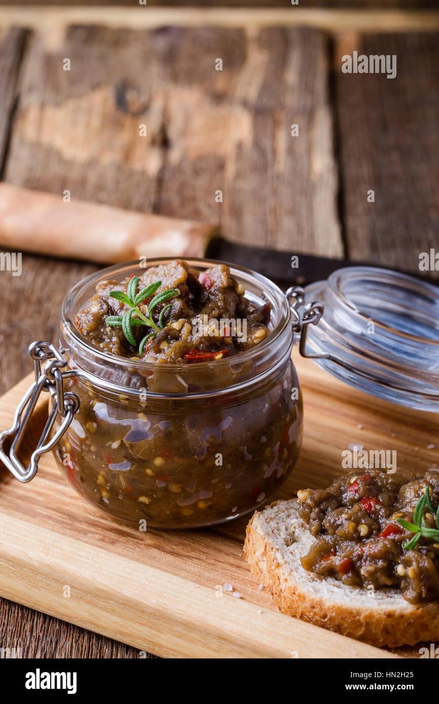 Des pate de l'aubergine. Coller dans un bocal en verre sur la table en bois rustique. La nourriture végétarienne Photo Stock