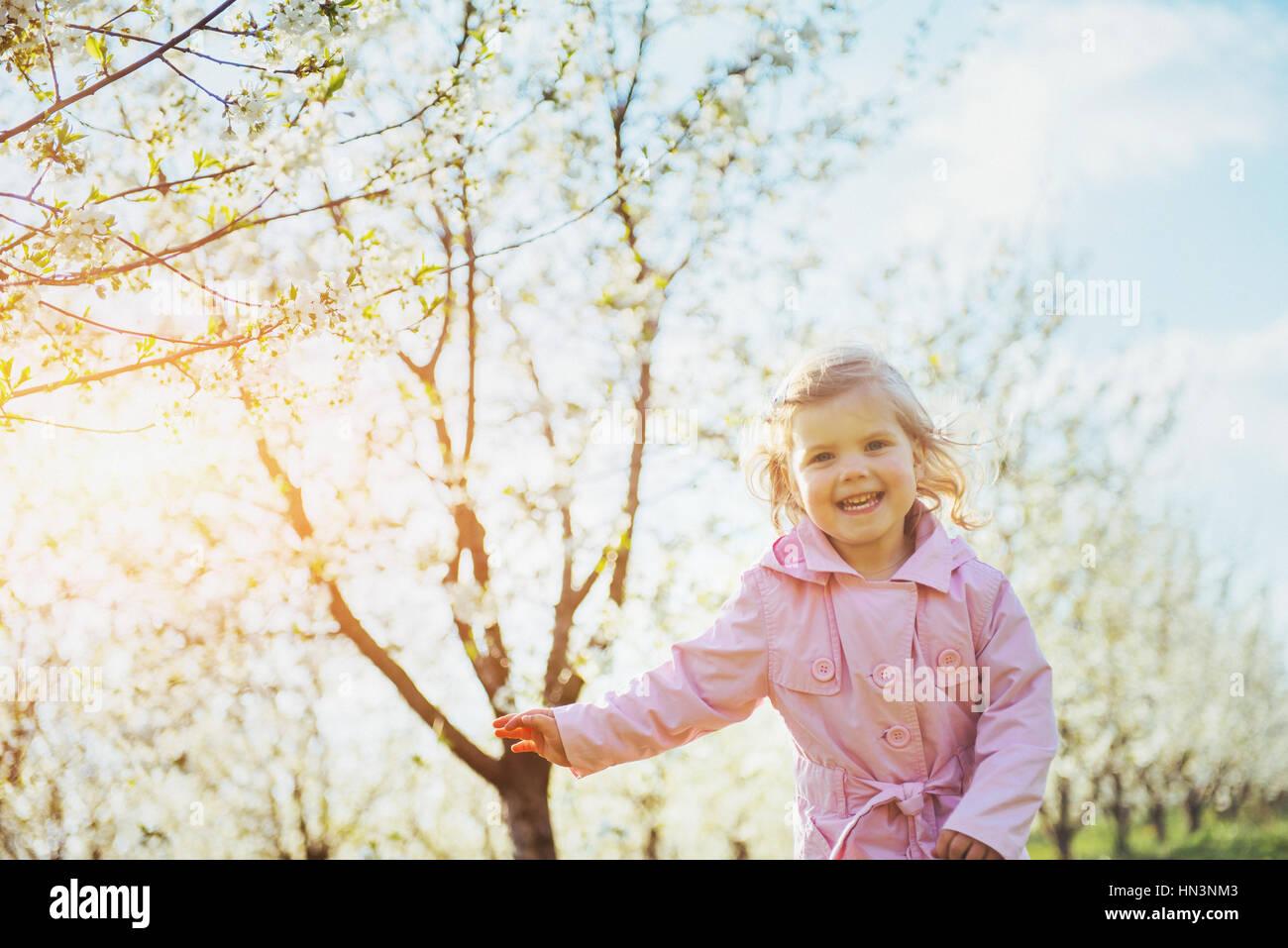 L'exécution de l'enfant en plein air arbres fleuris. Photo Stock