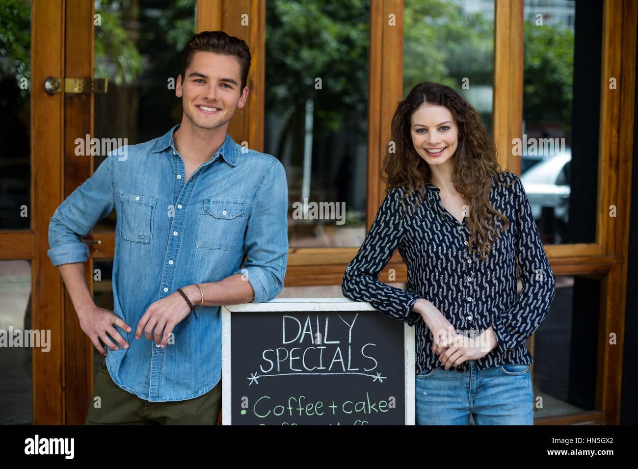 Portrait of smiling man and woman leaning on panneau de menu à l'extérieur de la cafe Banque D'Images